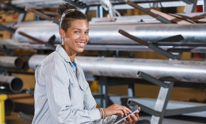 Woman works on computer tablet in a warehouse setting.