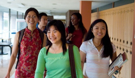 Smiling Asian students walking in a hallway