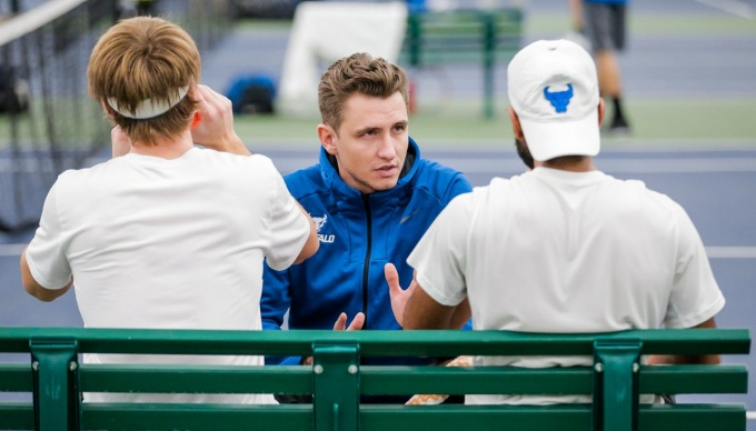 George Tibil talking to two UB tennis players on the bench.
