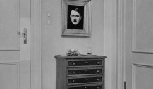 A room with a framed Hitler portrait hanging on the wall.