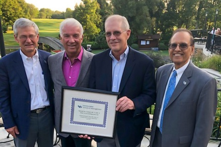 Kenneth W. Colwell and David Pfeil holding a plaque and standing with UB President Satish Tripathi and UB Provost Charles Zukoski at a golf course.