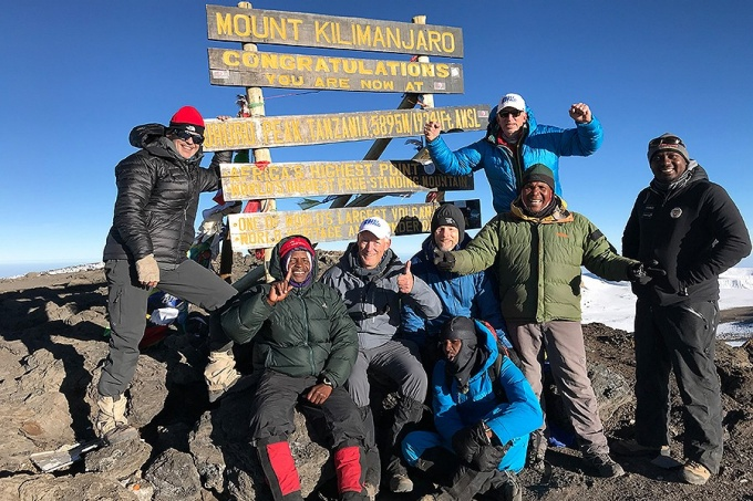 Scott Weber (bright, back row, arms raised) and friends climbed Mt. Kilimanjaro.
